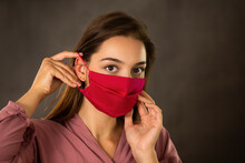 Woman Attaching Red Cloth Face...