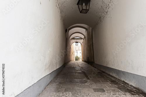 Fotomural Narrow inner paved stone urban street road passage in old european city