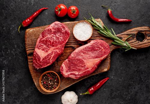 Fototapeta Two raw beef ribeye steaks with spices on a stone background obraz na płótnie