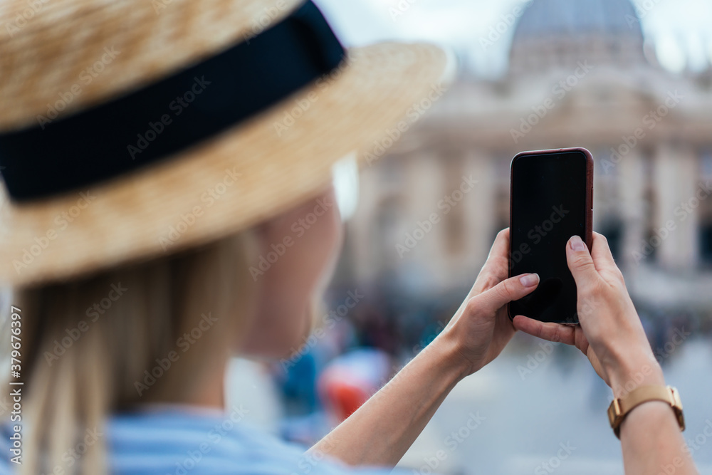 Fototapeta Woman taking photo with smartphone in Rome