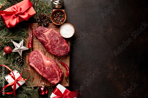 Raw ribeye beef steaks for preparing a dinner for two for a Christmas holiday on a stone table with a Christmas tree and Christmas tree decorations with copy space