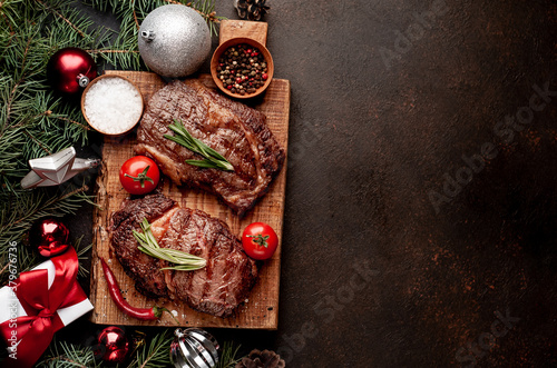 Christmas dinner for two, grilled beef steak, ribeye, greens and spices on a sto Fototapet
