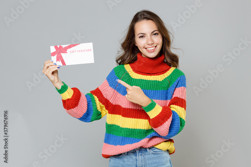 Obraz Smiling cheerful young brunette woman 20s wearing casual colorful knitted sweater standing pointing index finger on gift certificate looking camera isolated on grey colour background, studio portrait. - fototapety do salonu