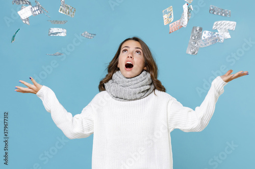 Shocked young woman wearing white sweater gray scarf throwing medication tablets pills isolated on blue background studio portrait Canvas Print