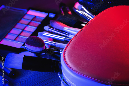 Cosmetic bag, makeup brushes, eyeshadows palette, lipstick and high heels shoes on the flat lay table background in the neon lights Wallpaper Mural