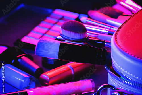 Cosmetic bag, makeup brushes, eyeshadows palette, lipstick and high heels shoes on the flat lay table background in the neon lights Poster Mural XXL