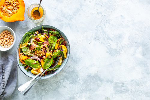 Fresh vegetable and pumpkin salad in a plate on a white stone background Fototapeta