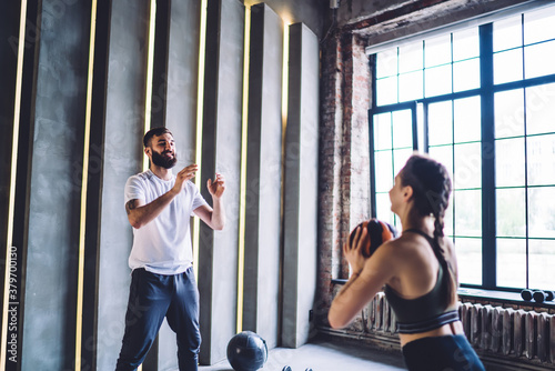 Man and woman throwing fitness ball