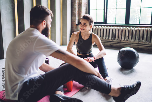 Fototapeta Happy young 20s woman having positive conversation with male trainer in gym discussing exercises and nutrition on consultancy, smiling couple in love satisfied with workout results share feedbacks obraz