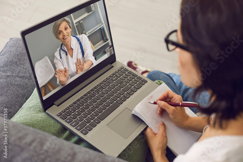 Obraz na plátně Woman patient making notes during online consultation with woman doctor consulti