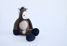 Children Toy Collection, Soft Brown Horse On A White Background. Copy Space