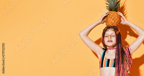 Photo Teenage girl with african pigtails, in colorful swimwear