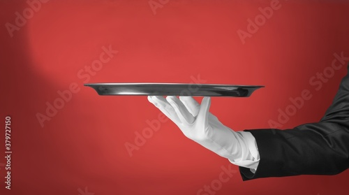 Elegant waiter hand in white glove holding an empty plate Canvas Print