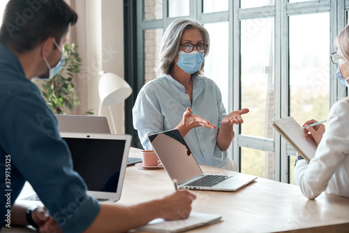 Fototapeta Old female mentor coach wearing face mask training young workers at group meeting in reopen office. Middle aged businesswoman teacher working with students at university class. Social distance concept obraz