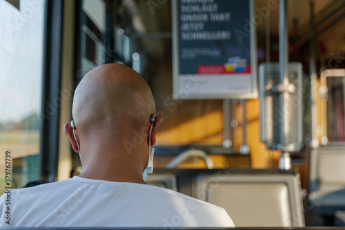 Tablou Canvas Interior and selected focus view at the back of male passenger with face protection mask and skinhead who sit in  tram or train in Germany during epidemic of COVID-19 virus with new normal concept