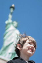 Boy Stands At The Base Of The Statue Of Liberty, Looking Over New York Harbor Harbor