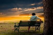 Man Sitting On Bench At Sunset