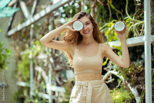 Fototapeta Cute young long-haired woman holding a coconut and smiling obraz