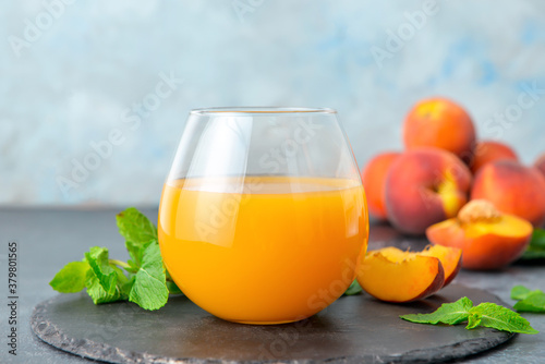 Glass of fresh peach juice on table