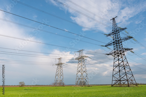 Papel de parede Electrical net of poles on a panorama of blue sky and green meadow