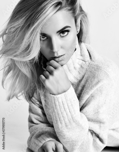 Fototapeta Black and white portrait of young sexy flirting blonde woman vamp in warm knitted sweater looking at camera obraz
