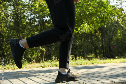 Fototapeta A man in a tracksuit running in the park in sunny morning obraz