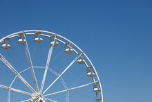 White Ferris Wheel Against A Blue Sky Background