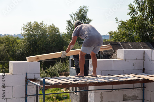A worker builds the walls of a house from aerated concrete bricks Wallpaper Mural
