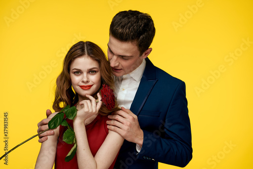 Valokuvatapetti lovers man and woman with a red rose in their hands hugging on a yellow backgrou