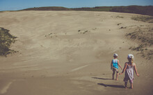 Two Little Girls Run Through The Sand Dunes.