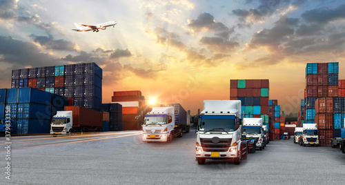 Fototapeta Container truck in ship port for business Logistics and transportation of Container Cargo ship and Cargo plane with working crane bridge in shipyard at sunrise, logistic import export and transport  obraz