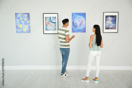 Man and woman at exhibition in art gallery Wallpaper Mural