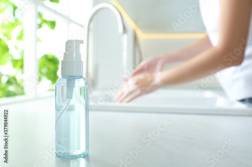 Bottle of antibacterial soap and blurred woman washing hands on background. Personal hygiene during COVID-19 pandemic