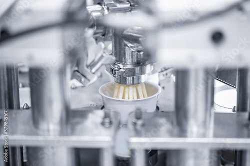 Fotografie, Obraz Automatic filling of sour cream into packaging
