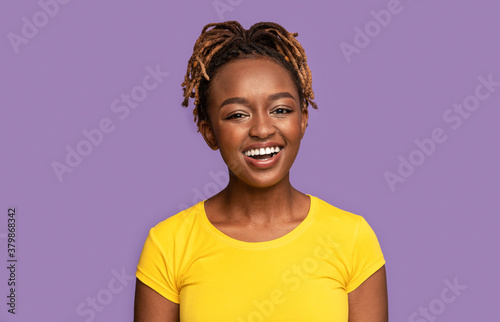 Fényképezés Young smiling african american woman over purple background