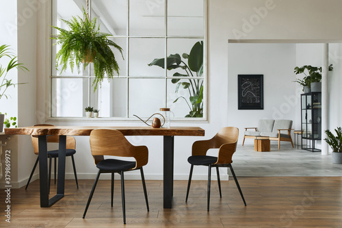 Stylish and botany interior of dining room with design craft wooden table, chairs, a lof of plants, big window, poster map and elegant accessories in modern home decor Fotobehang