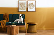 canvas print picture Stylish interior of living room with design furniture, gold pouf, plant, mock up poster frames, carpet, accessoreis and beautiful dog lying on the sofa in cozy home decor. Template.