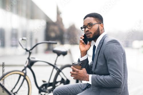 Foto Handsome businessman having business talk in park