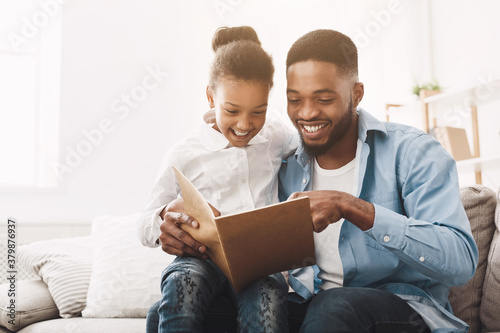 Carta da parati Happy evening. Afro dad reading fairy tale to his daughter