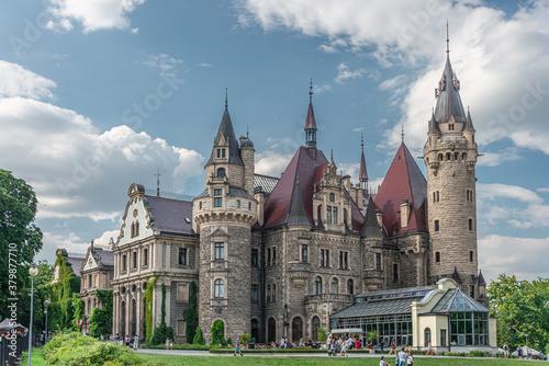 Obraz view of the Zamek w Mosznej. Moszna Castle - Beautiful castle and lilies in the foreground POLAND - fototapety do salonu