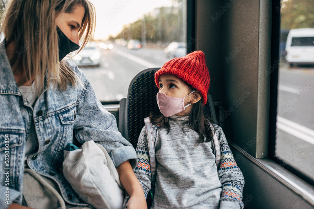 Fototapeta The kid in red hat and her mother wear protective face masks while going to school by bus during coronavirus. Worried little girl in protective face mask looking to her mom in the black medical mask.