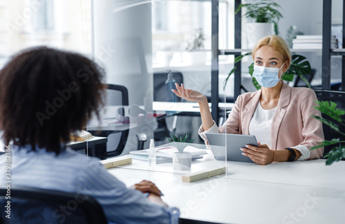 Fototapeta Modern hr and interview during coronavirus epidemic and health protection. Manager in protective mask asks african american woman questions through protective glass obraz
