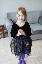 Pretty Little Red-haired Girl Dressed As A Witch Shows Off Her Home Made Cup Cake