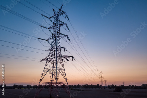 Obraz na plátně Transmission power, power tower on an empty farm land at the sunset