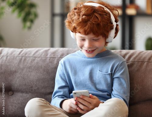 Slika na platnu Delighted redhead boy with smartphone sitting on sofa.