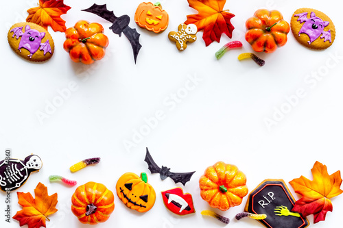 Frame of Halloween decorations with cookies and candies, top view