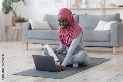 Fototapeta African Muslim Woman Choosing Online Tutorials On Laptop For Training At Home obraz