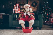 Full Length Photo Grey Beard Santa Claus Finish X-mas Christmas Midnight Gift Delivery Relax Sit Couch Soak Basin Hot Water Feet Close Cover Plaid Blanket Wear Red Cap In House Indoors