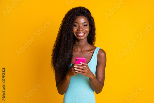 Photo portrait of happy african american woman holding pink phone in two hands smiling wearing blue singlet isolated on vivid yellow colored background
