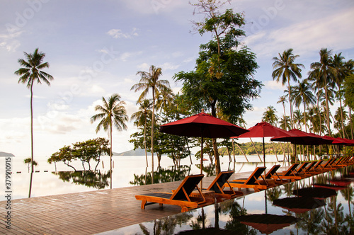 Photo Infinity edge pool under blue sky in summer with beach umbrellas